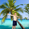 Royalty-Free Stock Photo: The happy teenager about a palm tree against ocean