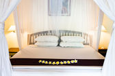 Wide bed under bed curtains — Stock Photo