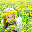 Young pretty woman in wreath of dandelions in the meadow solar day — Stock Photo #4645078