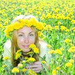 Young pretty woman in wreath of dandelions in the meadow solar day — Stock Photo #4645082