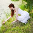 The beautiful girl in a white sundress on the bank of wood lake - Stock Photo