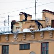 Russia. Petersburg. Workers clean snow and icicles from a house roof - Stock Photo