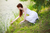 The beautiful girl in a white sundress on the bank of wood lake — Stock Photo