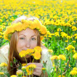 Young pretty woman in wreath of dandelions in the meadow solar day — Stock Photo #4765394