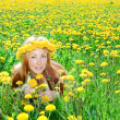 Young pretty woman in wreath of dandelions in the meadow solar day — Stock Photo #4765401