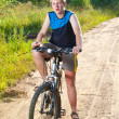Teenager goes on bicycle on country road — Stock Photo #4765457