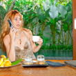 Stock Photo: Young beautiful womdrinks teand speaks by phone on tropical coun