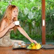 The young beautiful woman drinks tea and chooses fruit on a tropical countr — Stock Photo