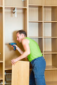 The man is engaged in repair and furniture assemblage — Stock Photo