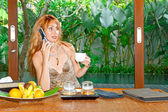 The young beautiful woman drinks tea and speaks by phone on a tropical coun — Stock Photo