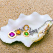 Стоковое фото: Exotic seshell with beads lies on sand