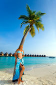 Young beautiful girl stands near by palm tree on background of ocean — Stock Photo