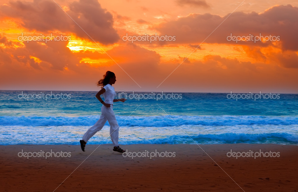 Silhouette of woman, running on sunset along ocean coast — Stock Photo #4910291