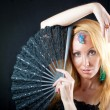 The beautiful young woman with long  blonde hair and  fan and jewellry — Stock Photo