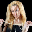 Beautiful young blonde woman with long hair and a pearl beads — Stock Photo