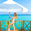 Young woman tans on a terrace of water villa on ocean Maldives — Stock Photo #5076271