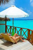 Giovane donna si abbronza su villa sull'oceano maldive — Foto Stock