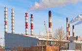 Thermal power station pipes smoke over a city — Stock Photo
