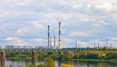 El puente ferroviario a través de las tuberías de río y fábrica — Foto de Stock