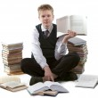 The schoolboy in a school uniform sits on a floor, near to packs of books, — Stock Photo