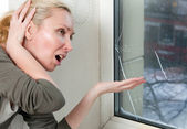 The housewife is upset, because the double-glazed window of bad quality has — Stock Photo