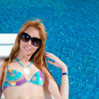 The beautiful woman in sun glasses sunbathes at pool — Stock Photo