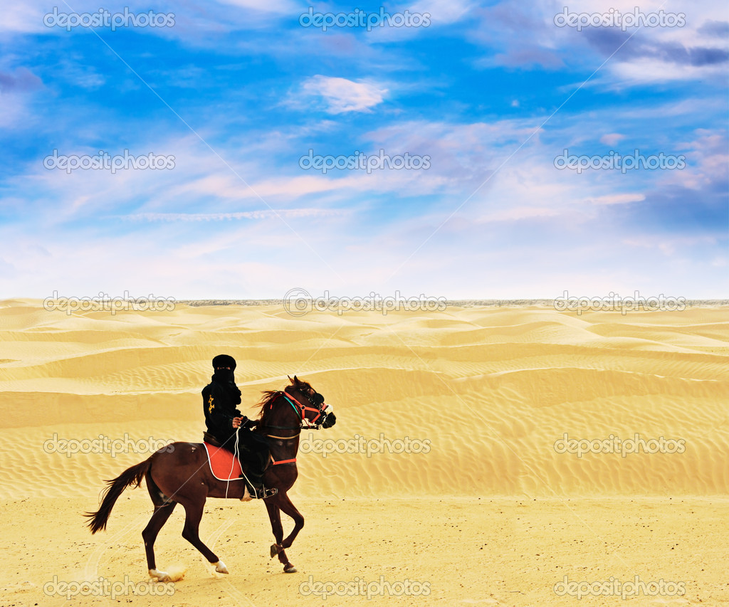 Bedouin on horse going through desert Sahara.  Stock Photo #3924254