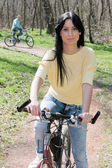 Young woman on bike outdoors — Stock Photo