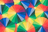 Guarda-chuva com as cores do arco-íris como plano de fundo — Foto Stock