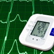 Digital blood pressure monitor with cardiogram in the background — Stock Photo #4451577