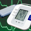 Digital blood pressure monitor with cardiogram in the background — Stock Photo #4451584