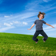 Child jumping on green field — Stock Photo