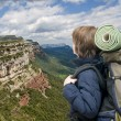Kid with a backpack on a mountain trip - Stock Photo
