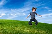 子供緑の野原にジャンプ — ストック写真