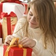 Girl with a christmas hat and a present — Stock Photo