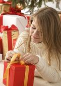 クリスマス帽子とプレゼントを持つ少女 — ストック写真