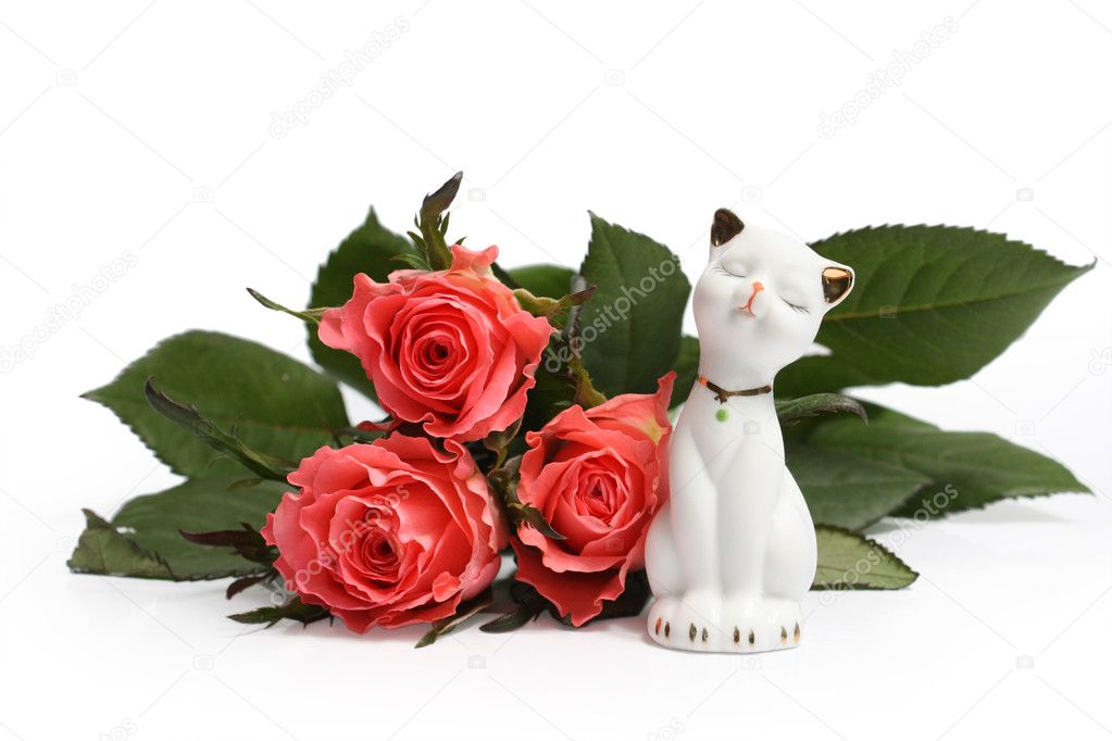 Cute cat figurine against the backdrop of pink roses — Stock Photo #5049755