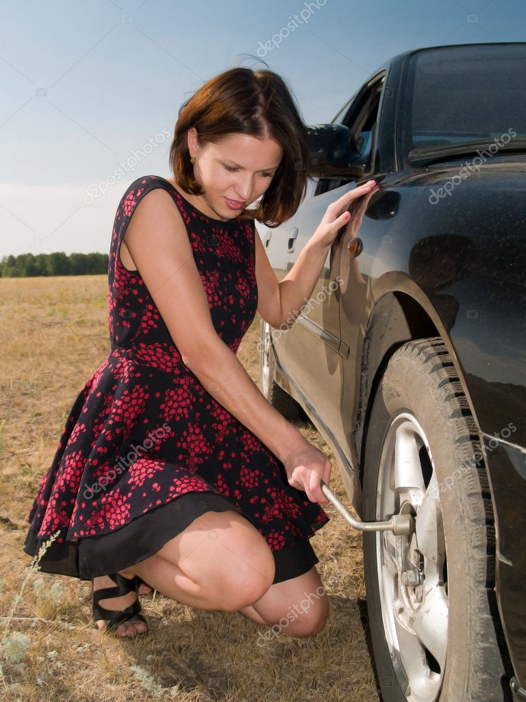 A beautiful young woman repairing a car, unscrew the wheel — Stock Photo #4978438