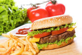Hamburger with fries and vegetables — Stock Photo