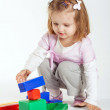 Little girl plays with cubes — Stock Photo