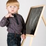 Little boy draws on blackboard — Stock Photo