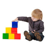 Little boy plays with colorful cubes isolated — Stock Photo