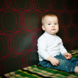 Little serious boy sitting near the wall — Stock Photo