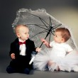 Little boy and girl sitting under umbrella — Stock Photo