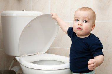 Little boy looks in the toilet