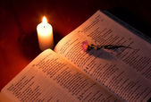 Bible by candle light — Stock Photo