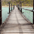 Wooden Suspension bridge over a lagoon — Stock Photo