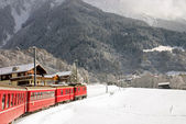 A red swiss train running through the snow. — Stock Photo