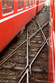 A railroad cross between two red swiss trains — Stock Photo