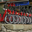 Stock Photo: Many red downhill bicycles for rent at the swiss railway station